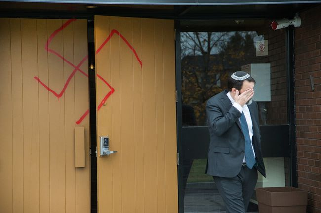 Joshua Dougherty wipes his eye as he comes through the doors at Congregation Machzikei Hadas, which was spraypainted with swastikas and hateful messages sometime over the night.