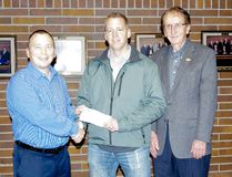 SERC emergency co-ordinator Chris Kalansky (left), along with Morden deputy mayor Irvin Wiebe (right), accepts a cheque for $10,000 from Andrew Plett (centre), Enbridge right of way agent, Nov. 16, 2016. (Alexis Stockford/The Morden Times)