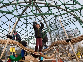Youngsters enjoys one of the play structures now open to the public as the city quietly opens the controversial Giver 150 Mooney's Bay playground.