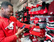 Calgary Stampeders running back Jerome Messam video chats with his girlfriend as he shops for a Stampeders toque for her in the Stamps Store at McMahon Stadium on Monday November 21, 2016. The Stamps are heading to Toronto tomorrow ahead of the Grey Cup next weekend.