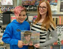 "Fort McMurray resident Julie Lodge holds a copy of ""Saving Thunder the Great"" with her son Jackson, 11. The book is based on Lodge's escape from the May 3 wildfire and her determination to bring the family gerbil, Thunder, with her. Supplied image/ Julie Lodge"