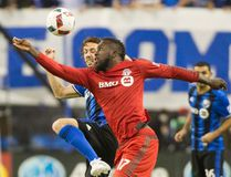 Toronto FC's Jozy Altidore fights for the ball with a Montreal Impact player during last night's game. (THE CANADIAN PRESS)