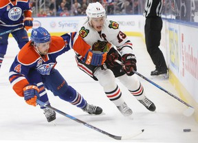 Kris Russell and Jonathan Toews battle for the puck during Monday's game at Rogers Place. (The Canadian Press)