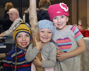 John Lappa/Sudbury Star Max Whissell, 3, left, and his sisters, Madison, 3, and Payton, 5, try winter apparel on for size at the Christmas craft show at Pioneer Manor in Sudbury on Friday. The event continues Saturday and Sunday from 10 a.m. to 4 p.m.