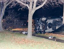 The mini van at rest on its side against the fence at Judith Gooderham Park. (Darryl Coote/The Goderich Signal Star)