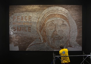 In this photo taken on Sunday, Nov. 27,  2016, Albanian artist Saimir Strati works on a mosaic portrait of Mother Teresa, at the Kosovo National Museum building in Pristina. Strati has built a portrait of Mother Teresa using staples, in a call for European countries to stop raising fences to shut their borders to refugees. (AP Photo/Visar Kryeziu)