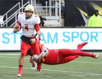 PETER POWER/CANADIAN PRESS Laval Rouge et Or Hugo Richard (4) is tackled by Calgary Dinos' Cory Robinson (77, of Airdrie) during first half of the University Sports Vanier Cup championship game in Hamilton, Ont., on Nov. 25. Laval won 31-26.