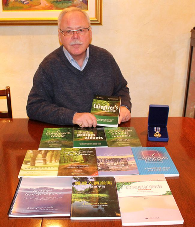 Robert Clarke is the recipient of a Governor General's Meritorious Service Decoration for spearheading the development of A Caregiver's Guide: A handbook about the end-of-life care. He is pictured here at his Chatham, Ont. on Monday November 28, 2016 with medal he received along several editions of the book, which has been translated into Chinese, Japanese, French, Portuguese and Inuktitut. Editions of the book have also been printed for distribution in Australia and New Zealand. (Ellwood Shreve/Chatham Daily News)