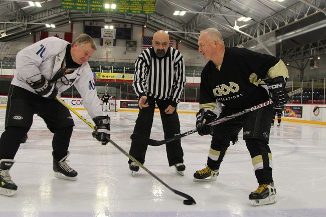 While these two team captains appear to be getting into some spirited competition at centre ice, Dr. Rick Kvas, left, and Rick Fiset were only having fun as heads of the top two fundraising teams for the hospital foundation's Face Off for Funds.  Fred Salvador, who acted as the official for the game between the two winning teams on Sunday, plays along by dropping the puck.
