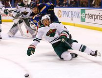 BILLY HURST/AP Minnesota Wild's Jared Spurgeon (front) falls to the ice as he and St. Louis Blues' Ty Rattie chase a loose puck during the second period of an NHL hockey game, Nov. 26 in St. Louis.