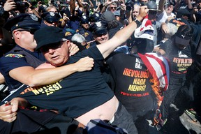 """In this July 20, 2016 file photo, a law enforcement officer takes Gregory """"Joey"""" Johnson into custody after he started to burn an American flag in Cleveland, during the third day of the Republican convention. President-elect Donald Trump said Tuesday that anyone who burns an American flag should face unspecified """"consequences,"""" such as jail or a loss of citizenship _ a move that was ruled out by the Supreme Court nearly three decades ago. (AP Photo/John Minchillo)"""