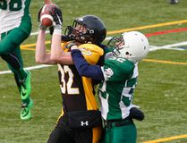 Adam Scott Lions' Cody Collier looks on as La Salle Black Knights' Logan Elliott hauls in a pass for a touchdown during the National Capital Bowl senior AA football game on Tuesday at Thomas A. Stewart Secondary School in Peterborough. (Clifford Skarstedt/Postmedia Network)