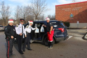 """From left to right: Strathroy-Caradoc Police Service Const. Mark Thuss, Deputy Chief Mark Campbell, Chief Laurie Hayman, and Const. Kevin VanRooyen making the first donations to this year's """"Cramp a Cruiser"""" campaign. JONATHAN JUHA/STRATHROY AGE DISPATCH/POSTMEDIA NETWORK"""