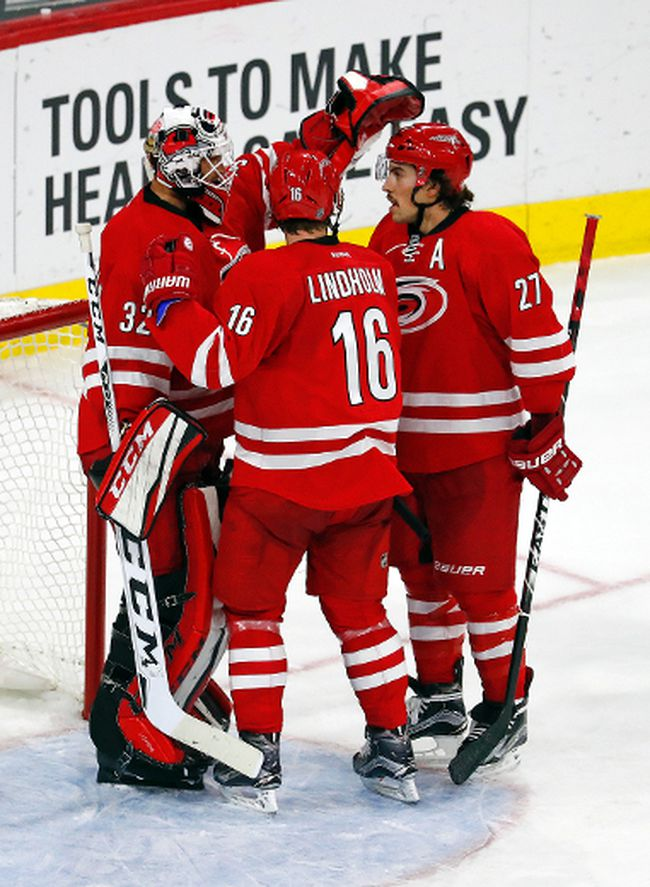 Carolina Hurricanes goalie Michael Leighton (32) celebrates with Elias Lindholm (16) and Justin Faulk (27) following the teams 3-2 win over the Florida Panthers, Sunday, Nov. 27, 2016, in Raleigh, N.C. (AP Photo/Karl B DeBlaker)