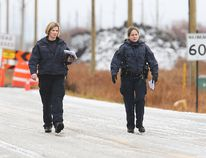 Two RCMP members search the area where a shooting near Raleigh and Glenway occurred Nov. 28. (Brian Donogh, Postmedia Network)