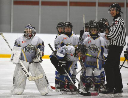 Referee Johnny Abele stands alongside the Delhi Rockets prior to a minor hockey contest last year. Centres within Norfolk County have found it difficult to attract new officials in recent years. EDDIE CHAU/POSTMEDIA