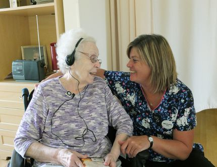 Woodingford Lodge resident Lois Smith (left) sits with Michelle Charlton, a personal support worker, as she listens to a musical playlist specifically curated for her through the Music & Memory program. (Submitted)