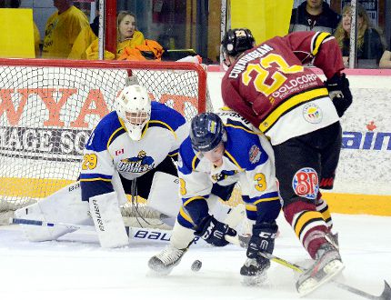 Kirkland Lake Gold Miners goalie Jeff Veitch gets low to stop a shot as defenceman Alex Olschewske takes out Timmins Rock forward Bain Cunningham with a hip check during the season opener at the McIntyre Arena on Sept. 10. The Rock announced on Thursday that they have acquired Veitch, a 19-year-old Mission, B.C., native, from the Gold Miners in a cash transaction. THOMAS PERRY/THE DAILY PRESS