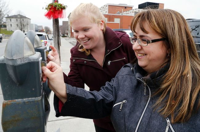 Luke Hendry/The Intelligencer  Food for Learning co-ordinator Kellie Brace, right, and community development co-ordinator Vicky Struthers insert coins into parking meters on Pinnacle Street Thursday in Belleville. Feed the Meter is an annual campaign supporting the school nutrition program.