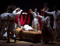 Lily, played by Charlotte Abbott, stares at a photograph in bed as cast members dance around her in a scene from the London Community Players' production of The Secret Garden. (CRAIG GLOVER, The London Free Press)