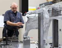 Leo Bourdeau uses a remote to control a coordinate measuring machine as he takes measurements of a beam, part of a Chrysler Jeep product, at Attica Manufacturing on Invicta Court in this file photo. (Free Press files)