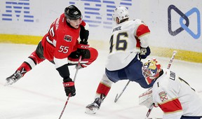 Senators forward Buddy Robinson (left) is checked off the puck by Florida Panthers' Aleksander Barkov as goaltender Roberto Luongo looks on during the second period on Saturday night at the Canadian Tire Centre. Robinson was recalled from AHL Binghamton, where he has seven points in 18 games this season. (WAYNE CUDDINGTON/POSTMEDIA NETWORK)