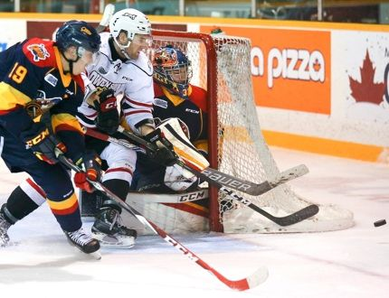 The Owen Sound Attack's Jonah Gadjovich, centre, and the Erie Otters' Dylan Strome, left, chase a puck into the corner past Otters' goalie Troy Timpano during Ontario Hockey League action on Saturday.