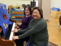 Members of the Porcupine community came out on Saturday to secure a piece of Whitney Public School history as the school board sold off its assets. In front is Pearl Fong-West, superintendent of business for District School Board Ontario North East and Diane Morrell, a financial analyst for the board, who tickled the ivories of this school piano that was being sold. The new owners of the former school will take over sometime this week.