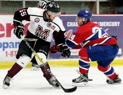 Chatham Maroons' Cale Markham, left, and Strathroy Rockets' Chris Wood battle for the puck in the first period Sunday at Memorial Arena. (MARK MALONE/The Daily News)
