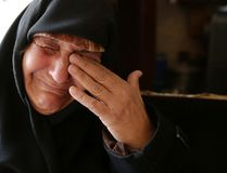 In this Sunday, Dec. 4, 2016 photo, Amina Hamawy cries after she returned to her looted home in the Hanano district of eastern Aleppo, Syria. It's a painful homecoming shared by hundreds of Syrians who are returning to areas devastated by years of war and then retaken from the city's embattled rebels in a recent government offensive. (AP Photo/Hassan Ammar)