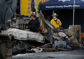 Crew workers walk behind debris from a warehouse fire in Oakland, Calif., Tuesday, Dec. 6, 2016. The fire erupted Friday, Dec. 2, 2016, killing dozens. (AP Photo/Jeff Chiu)