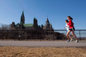 Joggers make their way through Majors Hill Park in downtown Ottawa in view of Parliament Hill on Wednesday, March 17, 2010. (THE CANADIAN PRESS/Sean Kilpatrick)