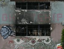 The front of The Ghost Ship warehouse damaged from a deadly fire is seen Wednesday, Dec. 7, 2016, in Oakland, Calif. The fire that killed 36 people during a party at an Oakland warehouse started on the ground floor and quickly raged, with smoke billowing into the second level and trapping victims whose only escape route was through the flames, federal investigators said Wednesday. (AP Photo/Eric Risberg)