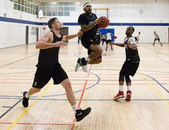 London Lightning player D'Vonne Pickett flies between players Taylor Black, left, and Jameel Williamson, right, as he shoots on the basket on the opening day of their basketball training camp at the YMCA Central Branch in London, Ont. on Friday December 2, 2016. (CRAIG GLOVER, The London Free Press)