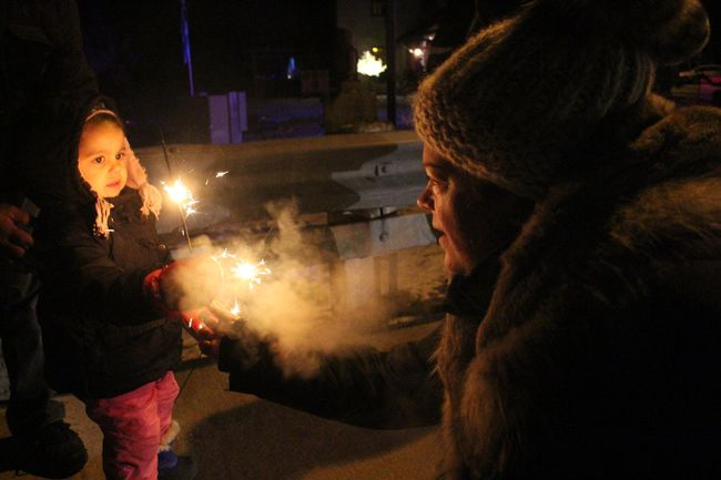 A young child warily accepts a sparkler from a parade participant during the Martintown Santa Claus Parade on Saturday December 10, 2016 in Martintown on Saturday December 10, 2016 in Cornwall, Ont. Greg Peerenboom/Cornwall Standard-Freeholder/Postmedia Network