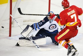 Calgary Flames TJ Brodie comes close to scoring on Winnipeg Jets goaltender Connor Hellebuyck during the third period of NHL action at the Scotiabank Saddledome in Calgary on Saturday December 10, 2016. GAVIN YOUNG/POSTMEDIA