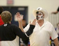 Mustangs fan Danny Thompson (grandfather of player Austin Thompson and coach JT Thompson) high fives a Mustangs player before the Bert Church Chargers senior boys basketball team beats the George McDougall Mustangs 77-72 in the Rocky View Sports Association playoff semifinal at Bert Church High School on Thursday, Mar 3, 2016 in Airdrie, Alta. Britton Ledingham/Airdrie Echo/Postmedia Network