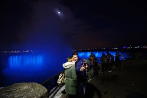 In this Saturday, Dec. 10, 2016 photo, people take a selfie near the Niagara Falls illuminated by new LED lights. (AP Photo/Julio Cortez)