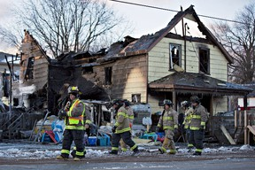 Firefighters survey the damage to a home in Port Colborne, Ontario, where a fire broke out overnight, leaving one person dead and three others who are believed to be part of the same family unaccounted for, on Wednesday, December 14, 2016. (THE CANADIAN PRESS/Aaron Lynett)