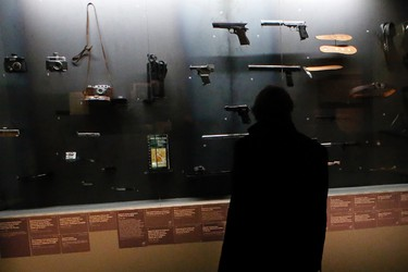 A visitor looks at real-life spy gadgets and weapons of secret agents around the world displayed as part of the 'Secret Wars' exhibition at Invalides Museum, in Paris, Monday, Dec. 12, 2016. (AP Photo/Francois Mori)
