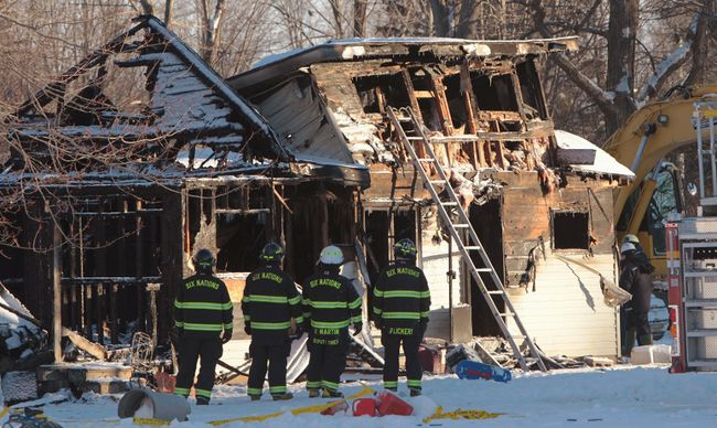 Fire fighters and Ontario Fire Marshall officials attend the scene of a house fire on Oneida Nation of the Thames, southwest of London, Ont., Thursday Dec. 15, 2016. (THE CANADIAN PRESS//Dave Chidley)