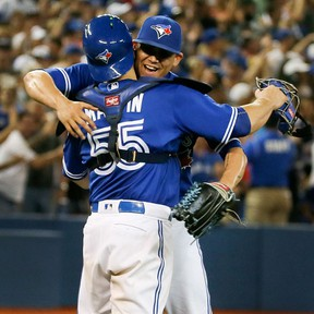 Toronto Blue Jays catcher Russell Martin and pitcher Roberto Osuna hug after a win at the Rogers Centre in Toronto on Aug. 13, 2016. (Veronica Henri/Toronto Sun/Postmedia Network)