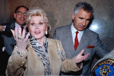 In a May 1, 1990 file photo, Zsa Zsa Gabor gestures as she while answering questions as she leaves the Beverly Hills courtroom where judge Charles Rubin ruled that she violated her probation. Gabor was ordered to complete her community service at a Venice homeless shelter, with an additional 60 hours. At right is her husband Frederick von Anhalt. (AP Photo/Kevork Djansezian, File)