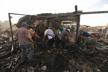Local residents comb through ashes and rubble at the scorched ground of Mexico's best-known fireworks market after an explosion explosion ripped through it, inTultepec, Mexico, Tuesday, Dec. 20, 2016.  (Eduardo Verdugo/AP Photo)