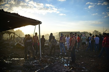 Rescuers and survivors remain amid the debris left by a huge blast that occurred in a fireworks market in Tultepec, Mexico on Dec. 20, 2016. (RONALDO SCHEMIDT/AFP/Getty Images)