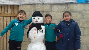 Syrian childen displaced from Aleppo City play in the snow in A'zaz, Syria in this handout photo. International aid organizations including World Vision are providing mattresses, blankets, heaters and fuel to families facing freezing conditions in the camps Handout/Postmedia Network