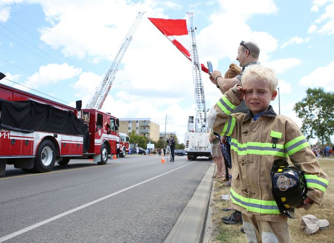 Cooper Brule, 4, watches thousands of Canadian Forces military personnel, firefighters, police and paramedics attend the memorial service for Loyalist Township firefighter Patrick Pidgeon in Amherstview, Ont. on Saturday, July 23, 2017. Pidgeon, a Loyalist Township firefighter, corrections worker and military policeman, died while fighting a fire on July 16. Elliot Ferguson/The Whig-Standard/Postmedia Network