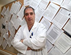 Dr. Adrian Baranchuk in front of some of his research papers he co-wrote at Kingston General Hospital. (Ian MacAlpine/The Whig-Standard)