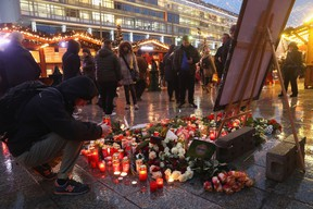 A visitor lays a candle at a makeshift memorial inside the reopened Breitscheidplatz Christmas market only a short distance from where three days ago a truck plowed into the market, killed 12 people and injured dozens in a terrorist attack on December 22, 2016 in Berlin, Germany. The Breidscheidplatz Christmas market is reopening today, though its small amusement rides and bright lights displays will remain shut off in a sign of continuing mourning for the attack victims. Meanwhile police have launched a European-wide manhunt for Anis Amri, a 24-year-old Tunisian man they suspect of having driven the truck. (Photo by Sean Gallup/Getty Images)
