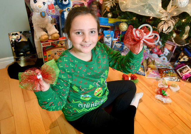 Ebonee Rebelo, 8, shows the decorative bows she made to raise funds for Christmas gifts for kids at Children's Hospital in London. In the background are some of the more than $800 worth of toys provided by her project, which she called Ebby Knows Bows. (Scott Wishart/Stratford Beacon Herald/Postmedia Network)